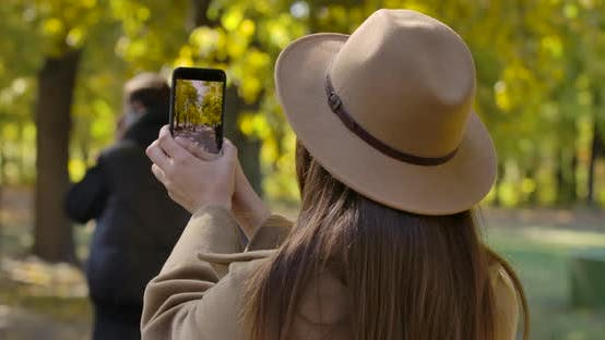 Thumbnail for Back View of Young Caucasian Girl in Brown Hat Taking Photos of Autumn Park on Her Smart Phone