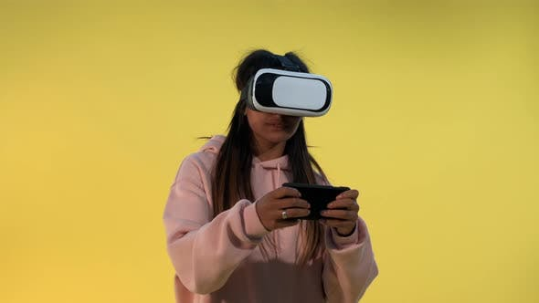 Thumbnail for Multiracial Girl in Virtual Reality Glasses Playing Online Games on Smartphone