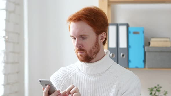 Thumbnail for Browsing Online on Smart phone, Man with Red Hairs