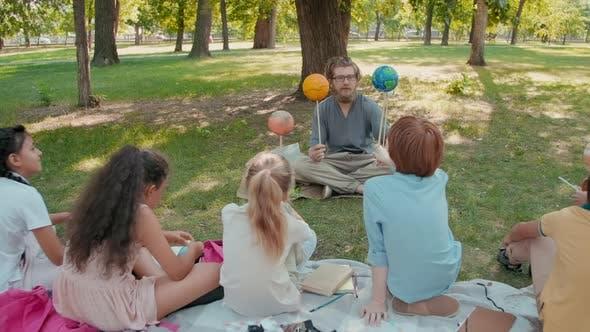 Schoolchildren Learning about Solar System in Park