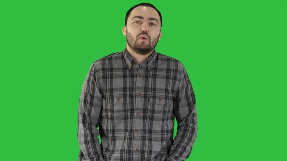 Young man walking and whistling on a Green Screen, Chroma Key