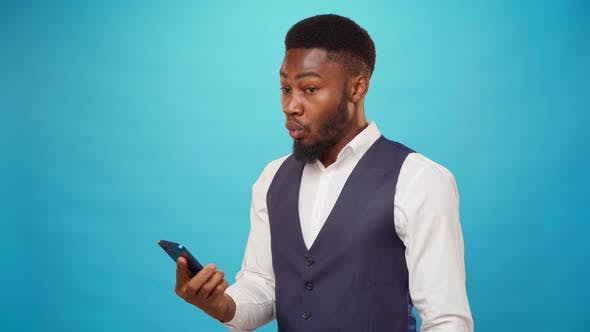 Surprised Black Man Reading a Message on His Phone