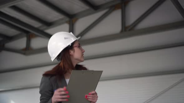 Thumbnail for Young Woman in a Helmet Scared Off at a Construction Site. The Boss Woman in a Suit Keeps Records of