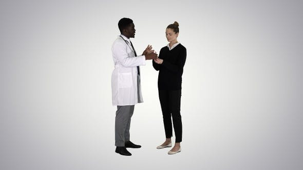 Thumbnail for Male Doctor Offers Medication to Young Woman on Gradient