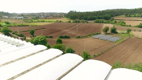 Countryside View with Greenhouses, Solar Panels and Tractor Working in the Agriculture Field