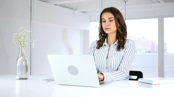 Cover Image for Serious Hispanic Woman Working On Laptop in Office