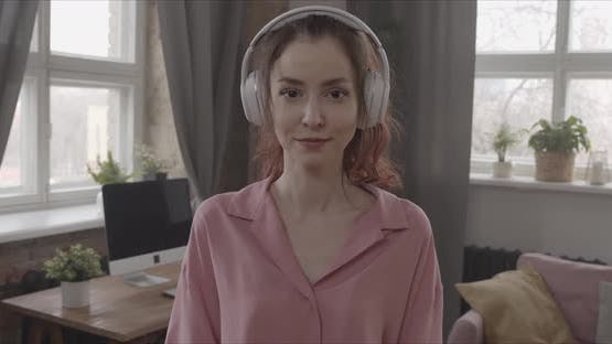 Girl Listening To Music With Headphones Looking Straight Into The Camera