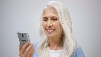 Senior Woman Scrolling Online Indoors
