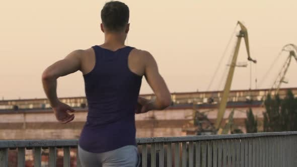 Thumbnail for Man Running Along Bridge, Developing Muscles of Legs and Respiratory System