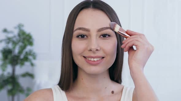 Thumbnail for Attractive young woman using make up brush to applying make up.