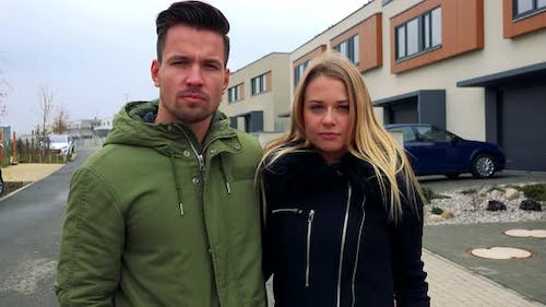 A Young, Attractive Couple Stands on a Road in a Neighborhood and Shakes Their Heads - Rejection
