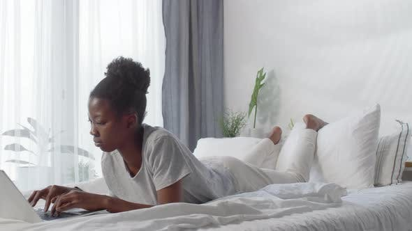 Thumbnail for Woman Browsing Internet with Laptop in Bed