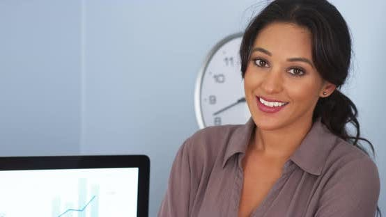 Thumbnail for Close up of smiling Hispanic business woman in office looking at camera