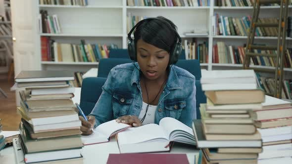 Thumbnail for Atractive African Young Woman Listening Music Making Some Note from note Book for University