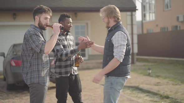Cover Image for Two Caucasian and African American Men Standing in Front of Big House Drinking Beer. The Third