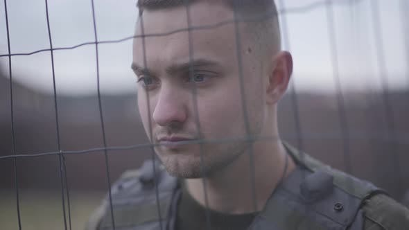 Thumbnail for Close Up Face of the Soldier Standing in His Bulletproof Vest Behind the Net. A Man Is in the