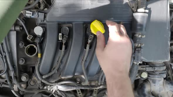 Cover Image for Close Up of a Male Hand Fill a Car Engine By Oil.