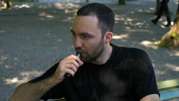 Thumbnail for Man smoking the vape outdoors.