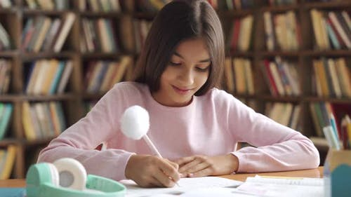 Smiling Indian Latin Preteen School Girl Pupil Studying at Home Sitting at Desk