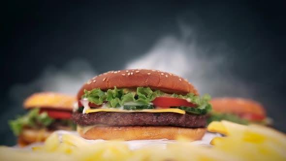 Thumbnail for Frische leckere gegrillte Burger rotieren auf schwarzem Rauchhintergrund. Fast Food Konzept
