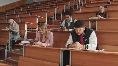 University Students Scrolling through Smartphones in Class