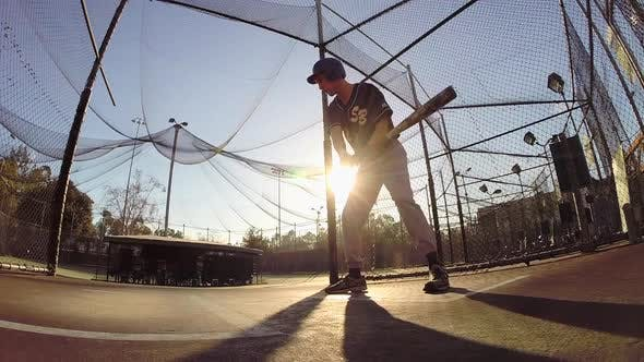 A baseball player practicing at the batting cages.