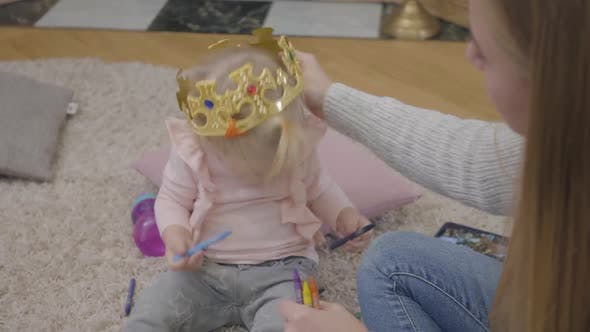 Thumbnail for Close-up of Young Caucasian Mother Trying To Put Toy Crown on Daughter's Head