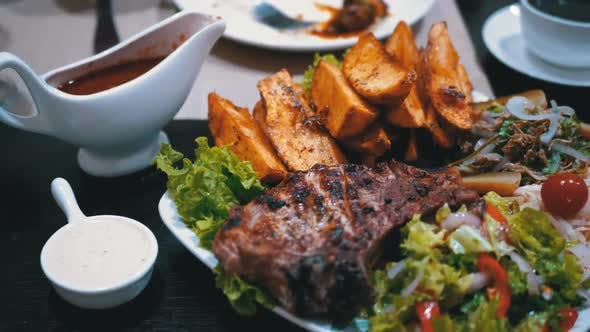 Cover Image for Steak on Ribs with Potatoes and Salad on a Table in a Georgian Restaurant