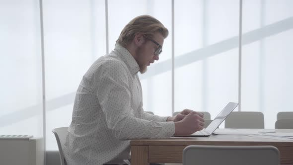 Thumbnail for Portrait Handsome Blond Thoughtful Businessman in Glasses Sitting at the Table in a Light
