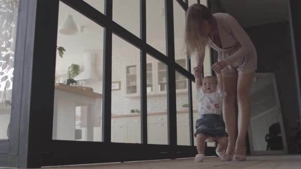Thumbnail for Cute Woman and Her Baby Girl Standing on the Floor at Home. The Child Making First Step, Mother