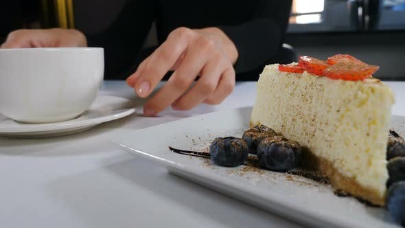 Male Hands Putting White Plate with Cake on Table in Front of Female Guest. Waiter Serving Dessert