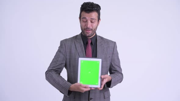 Thumbnail for Happy Bearded Persian Businessman Showing Digital Tablet and Looking Surprised