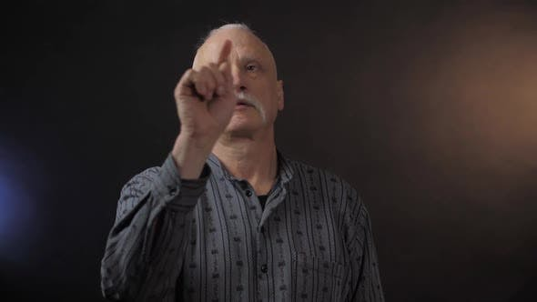 Thumbnail for Grey Haired Elderly Man Taps on Imaginary Screen with Finger