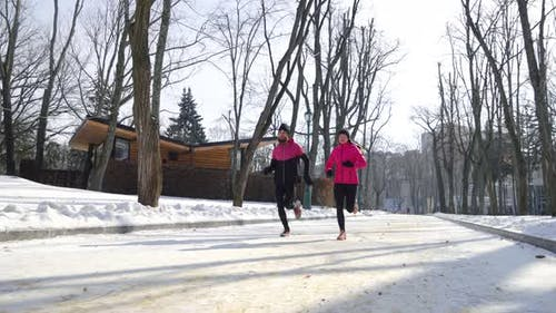 Jogging en duo athlétique dans le parc d'hiver