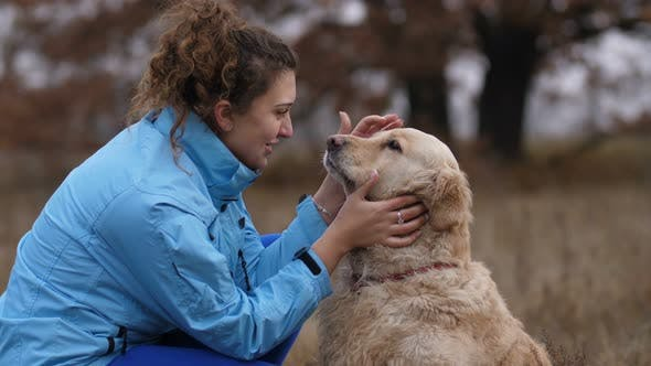 Positive Woman Bonding with Her Dog Outdoors