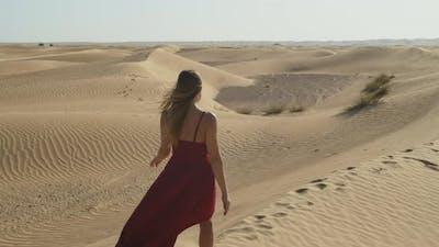 Beautiful Woman in Red Dress is Walking on Sand Wearing Red Dress