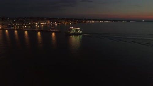Flying over touristic ship finishing night sea tour