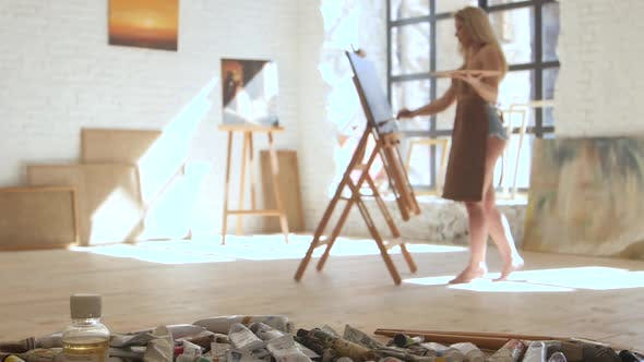 Thumbnail for Artist Paints Picture of Oil Standing Barefoot on Floor Studio