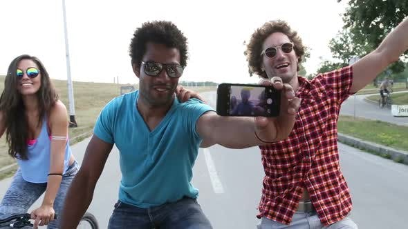 Thumbnail for Three young adults on bikes taking selfies with phone