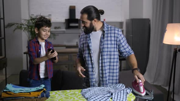 Single Handsome Father Ironing Clothes at Home