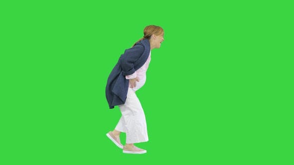 Walking Pregnant Woman Has Labour Pain Due To the Contraction on a Green Screen, Chroma Key.