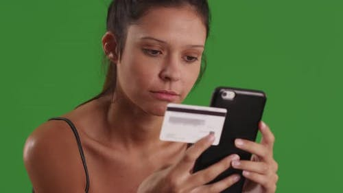 Happy young woman using smartphone to buy merchandise on internet on greenscreen