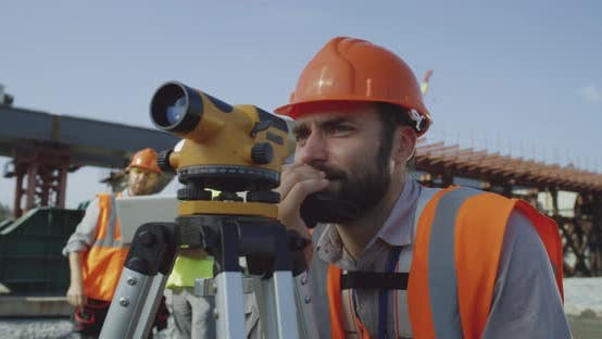 Thumbnail for Male Surveyors Using Theodolite Together