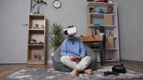 Thumbnail for 10-Aged Boy Sitting on Inflatable Sofa Sack Playing Games with Joystick Using Special VR