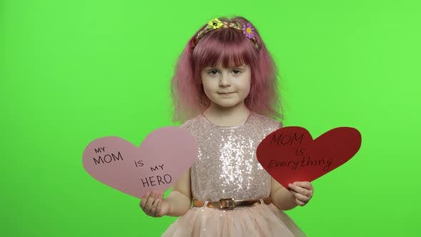 Thumbnail for Child Girl Princess Holds Two Paper Hearts with Text About Mother. Mother's Day