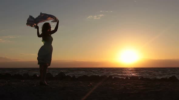 Thumbnail for Joyful Woman with Flying Scarf on Beach at Sunset