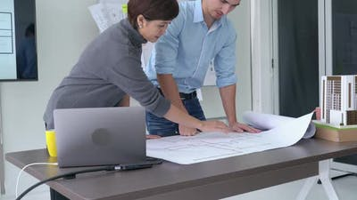Business people working on paper blueprint