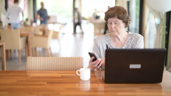 Thumbnail for Senior Woman Using Phone And Laptop At The Coffee Shop