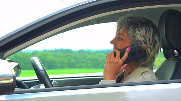 Thumbnail for Middle Aged Woman Sits in the Car and Calls with the Smartphone - Car Stands on the Verge of Road