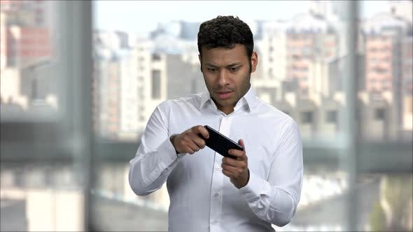 Excited Indian Man Playing Online Games with a Smart Phone
